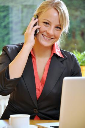 Junge Frau am Laptop telefoniert