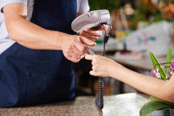 Hand überreicht Kreditkarte zur Bezahlung