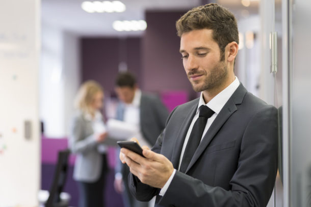 Businessman typing a message on smart-phone in modern office