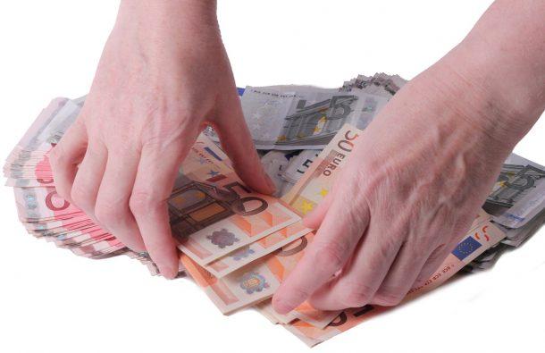 Kredit für die Gründungsphase: Hände sammeln Geldscheine auf